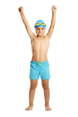Full length portrait of a boy wearing swimming trunks holding his hands up isolated on white background