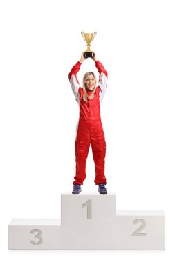 Happy female racer celebrating win on a winner's pedestal with a gold trophy cup isolated on white background