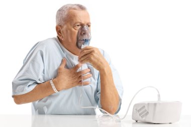 Elderly patient having chest pain and using an inhalator isolated on white background