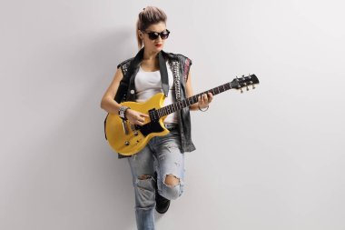 Female punker in a leather vest leaning on a wall and playing a guitar