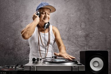 Mature dj with headphones playing music at a turntable against a grey wall
