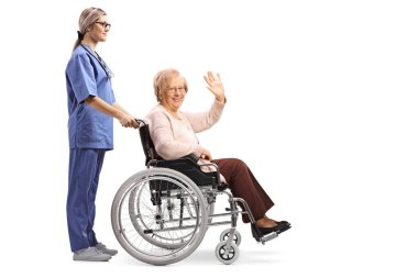 Full length profile shot of a nurse pushing a senior woman in a wheelchair waving isolated on white background