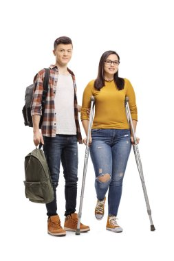 Full length portrait of a male student helping a female student walking with crutches isolated on white background