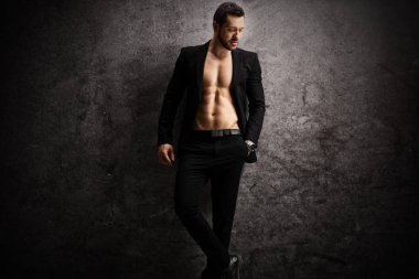 Male model in black suit posing shirtless