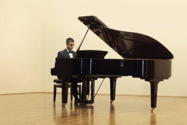 Pianist playing a grand piano in a salon isolated on white background
