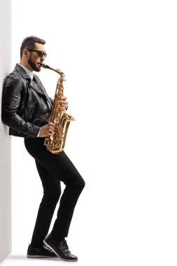 Full length profile shot of a handsome young male musician in a leather jacket playing a saxophone and leaning on a wall isolated on white background