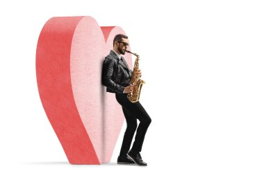 Full length profile shot of a male musician in a leather jacket playing a saxophone and leaning on a red heart isolated on white background