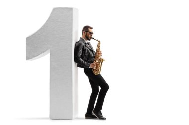 Full length profile shot of a young male musician in a leather jacket playing a saxophone and leaning on number one isolated on white background