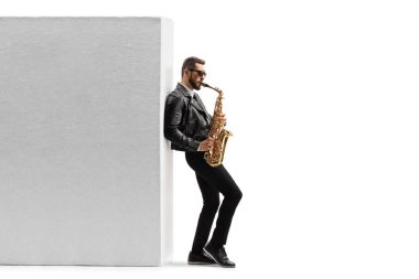 Full length profile shot of a male musician in a leather jacket playing a saxophone while leaning on a wall isolated on white background
