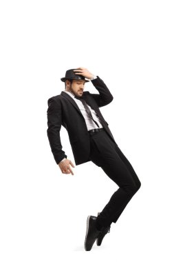 Full length shot of a man in a suit and hat dancing on tiptoes isolated on white background