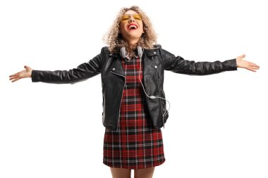 Young woman in a leather jacket spreading her arms and wearing headphones around her neck isolated on white background