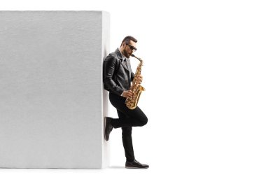 Full length profile shot of a guy playing a saxophone and leaning on a wall isolated on white background