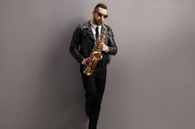 Man in a leather jacket playing a saxophone and leaning on a gray wall