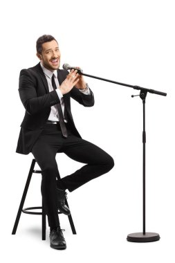 Young man in a suit sitting on a chair and singing on a microphone isolated on white background