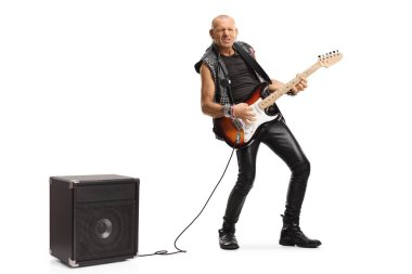 Full length portrait of a bald musician playing a guitar plugged into an amplifier isolated on white background