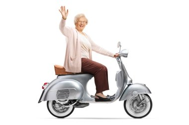 Profile shot of an elderly woman riding a vintage silver scooter and greeting with hand isolated on white background