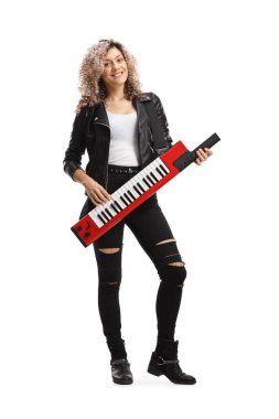 Full length portrait of a young female musician playing a keytar synthesizer isolated on white background