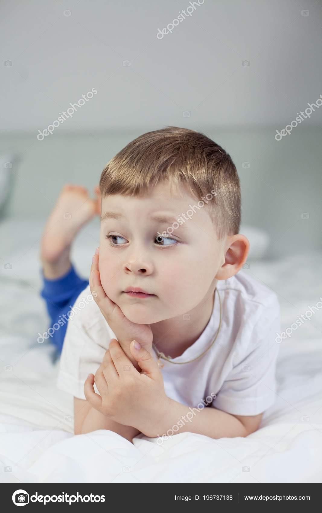 mignon petit gar on est allong sur le lit un gar on de 4. Black Bedroom Furniture Sets. Home Design Ideas