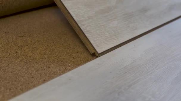 zavřít instalaci dřevěné laminátové podlahy na korkový podklad. renovace dřevěných podlah.