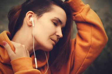 Beautiful Young Woman with Earphones Outdoors Enjoy Music. Hipster Girl Traveling