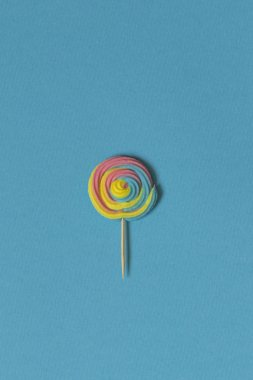 Creative view of colorful, handmade swirl lollipop in summer colors on blue paper background. Minimalism. Abstraction. Creativity. Top view.