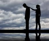 Fotografia Una silhouette di una donna moralmente supporta un uomo triste. Il concetto di supporto e assistenza