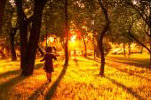 A kislány a lenyugvó nap sugarain fut. gyönyörű sziluett egy gyermek naplementekor