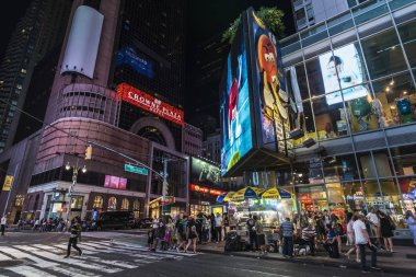 New York City, USA - July 30, 2018: Crowne Plaza Times Square Manhattan at night on Broadway Avenue next to Times Square with people around and large advertising screens in Manhattan in New York City, USA