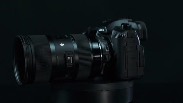 TOMSK, RUSKO - 28. května 2020: Panasonic Lumix DMC-GH5 kamera s rychloposuvníkem Metabones 0.71 ultra a sigma 18-35 1.8 art stojící na černém gramofonu, Micro Four Thirds System, černé pozadí