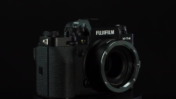 TOMSK, RUSSIA - May 28, 2020: FUJIFILM X-T4 body with Fringer ef-fx proII adapter standing on a black rotate stand, black background