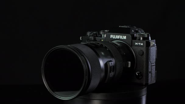 TOMSK, RUSSIA - May 28, 2020: FUJIFILM X-T4 body with Fringer ef-fx proII adapter and sigma 18-35 standing on a black rotate stand, black background