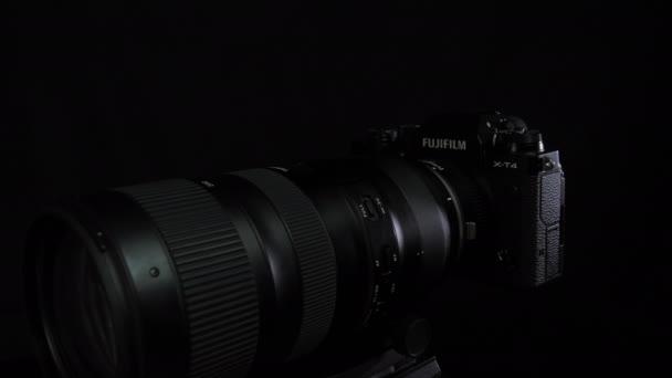 TOMSK, RUSSLAND - 28. Mai 2020: FUJIFILM X-T4 Karosserie mit Fringer ef-fx proII Adapter und Tamron 70-200 G2 auf schwarzem Drehstativ, schwarzer Hintergrund