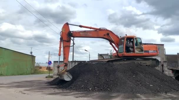 Petrohrad, Rusko-20. srpna 2019: ryšák z housenky Doosan Daewoo do nákladního auta vlije asfaltové drobky.