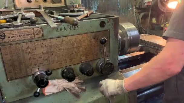 A Turner eltávolítja a hengert a esztergálásról és marógépről. Termék esztergálás a rajz szerint. Köszörűkő. Ipargyár.