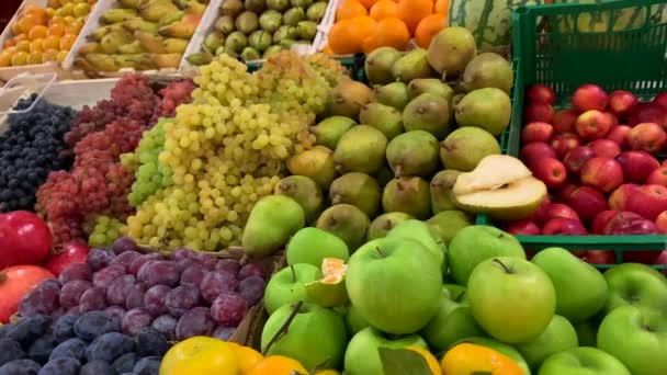 A variety of delicious natural fruits in wooden crates on a counter in the market. Grapes, lemon, apples, pears, tangerines, persimmons, plums, pomegranates, watermelon, oranges.