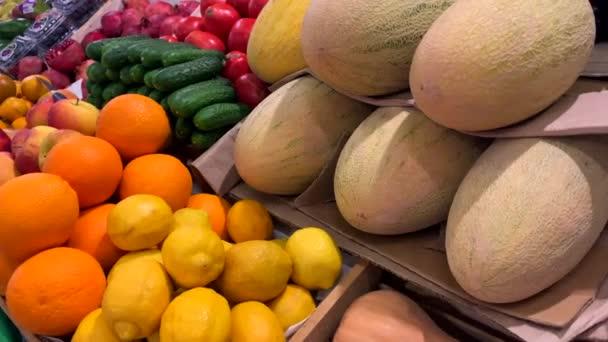Různé přírodní ovoce a zelenina na pultu na trhu. Rajčata, okurky, meloun, citron, pomeranče, jablka, granátová jablka, persimony.