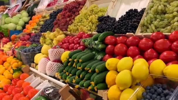 Různé přírodní ovoce a zelenina na pultu na trhu. Rajčata, okurky salátové, meloun, citron, hrozny, švestky, hrušky, mandarinky, pomeranče, jablka, granátová jablka, persimony.
