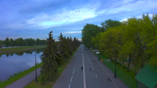 ST. PETERSBURG, RUSKO - 5. června 2020: Dvě holčičky jezdí na skútrech po silnici podél parku. Procházka podél říčního kanálu při západu slunce. Rozpětí přes silnici.