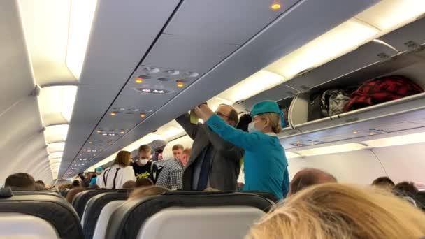 SAINT PETERSBURG, RUSKO - 25. srpna 2020: Letuška pomáhá cestujícím ukládat zavazadla na horní palandu. Lidé v ochranných maskách jdou do kabiny letadla.