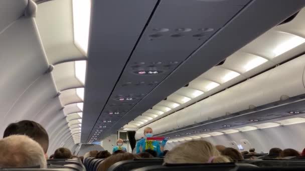 SAINT PETERSBURG, RUSKO - 25. srpna 2020: Letuška s modrým obličejovým štítem a ochrannými rukavicemi vysvětluje cestujícím v letadle, jak používat bezpečnostní pás.