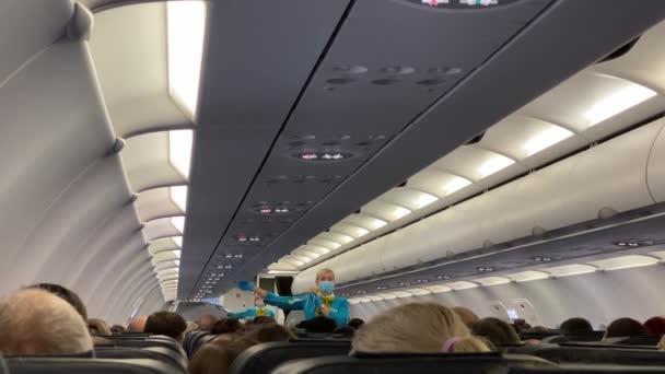 SAINT PETERSBURG, RUSKO - 25. srpna 2020: Letuška v modrém ochranném štítu a ochranných rukavicích vysvětluje cestujícím v letadle, jak používat kyslíkovou masku.