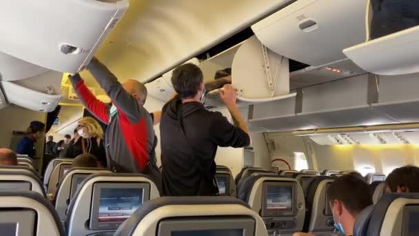 PETROPAVLOVSK-KAMCHATSKY, RUSKO - 15. ZÁŘÍ 2020: Cestující v letadle s ochrannými maskami položili svá zavazadla na horní palandu a sedli si na svá sedadla.