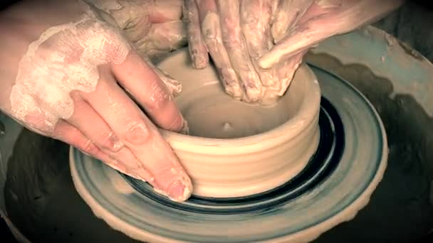 Workshop molding of clay on potters wheel. Dirty hands in the clay.