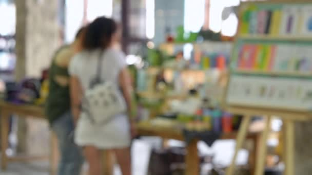 Blurred Background. Woman standing near the counterand buys things