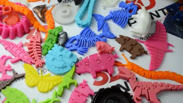 Many bright multi-colored objects printed on a 3d printer lie on a flat surface