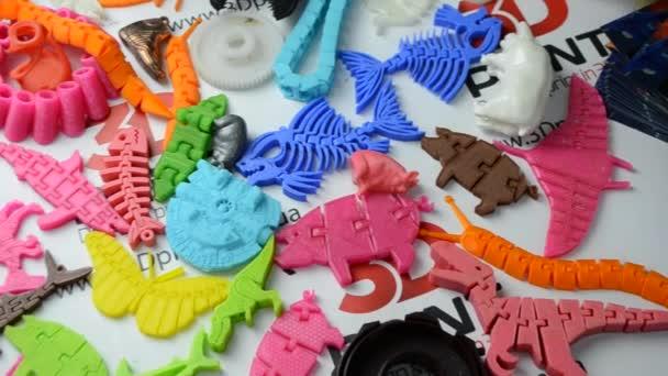 viele helle mehrfarbige Objekte, die auf einem 3D-Drucker gedruckt werden, liegen auf einer ebenen Oberfläche
