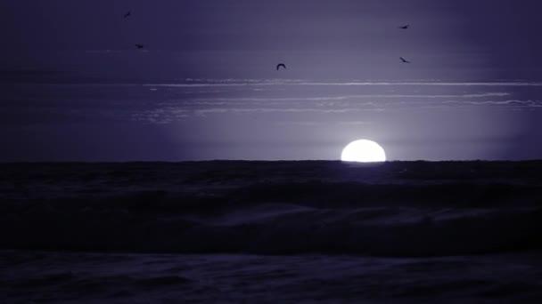 Bílý měsíc na obzoru nad mořem.