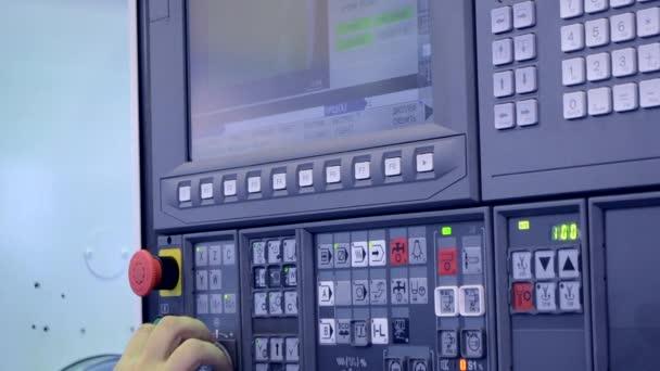 Der Mann am Bedienpult arbeitet mit einer Industriemaschine in Großaufnahme.