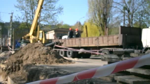 Pracovníci stavebního jeřábu pokrývají nové vodovodní trubky s betonovými deskami