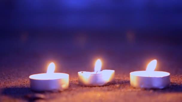 Három kis gyertya tabletta feküdjön a homokos tengerpart közelében a hullámok